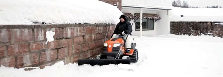 A riding mower snow plow in action.
