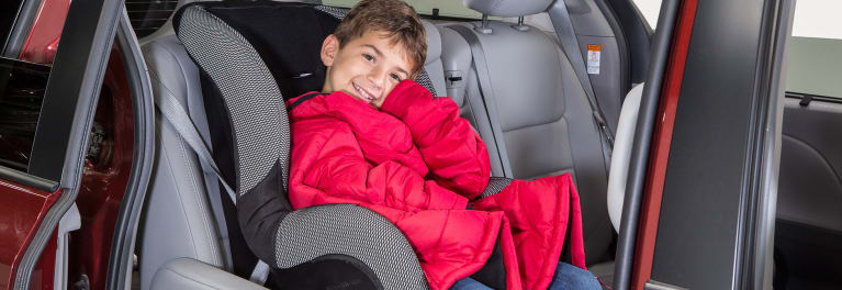 Child wearing a winter coat in a car seat