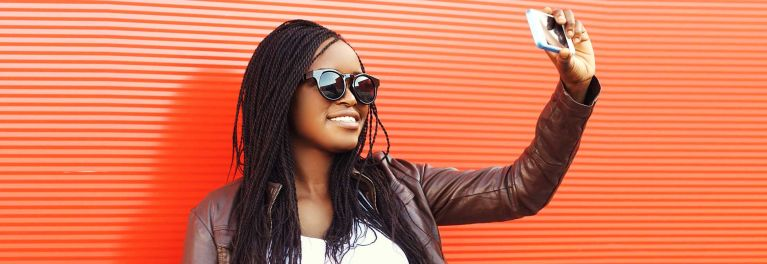 List of best smartphone cameras illustrated by a young woman taking a selfie