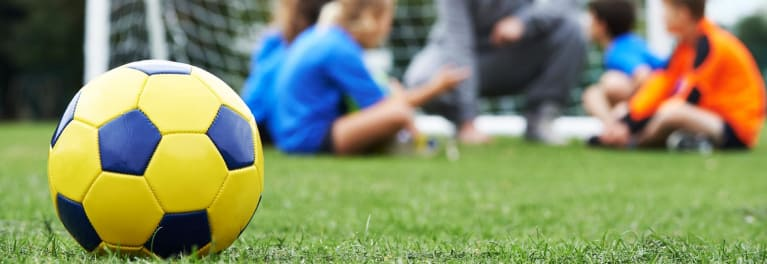 A close-up of a soccer ball near children huddled around the goal for an article on how to shoot great sports video.