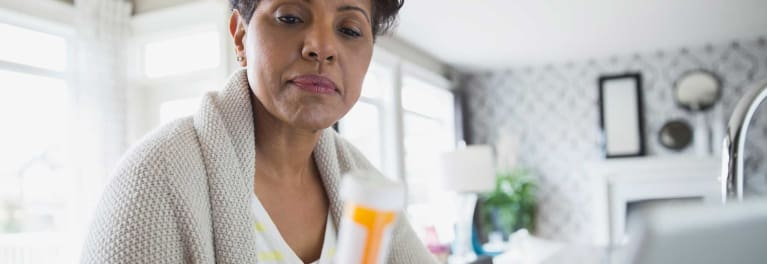A woman looking at a pill bottle, which might contain diuretics.