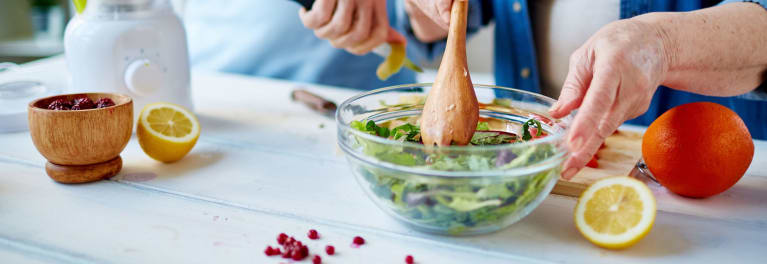 Woman making a salad. If you want to know how to lose weight, healthy eating is essential.