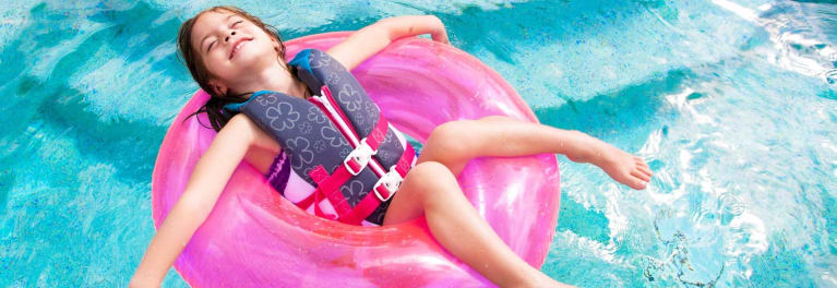 A child wearing a life vest in a pool.