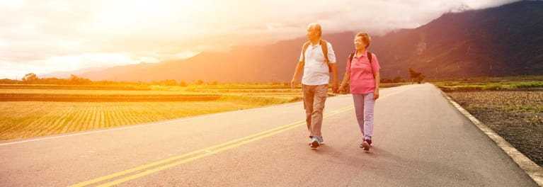 A man and a woman walking on a highway.