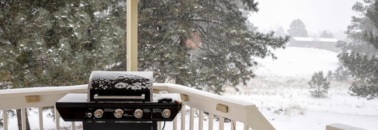 Gas grill on a deck ready for cold-weather grilling.