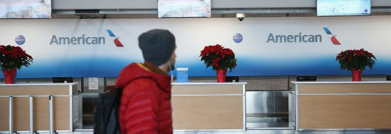 A man in a red coat in front of an airline ticketing desk.