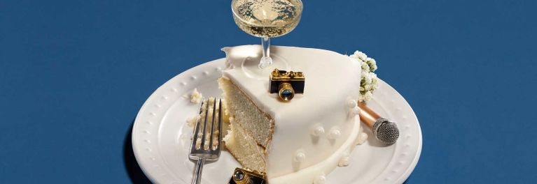 A slice of wedding cake with a camera, microphone and glass of champagne