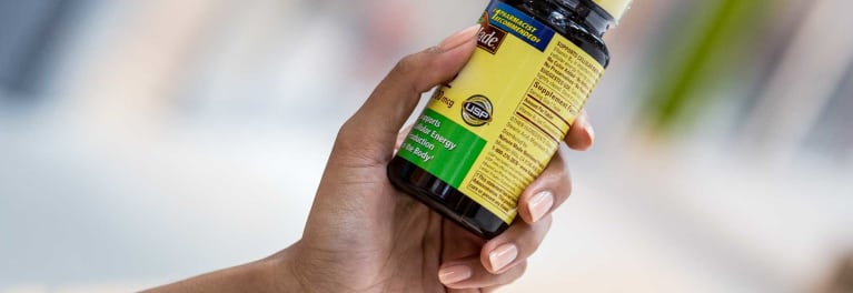 Hand holding a vitamin bottle that says USP verified
