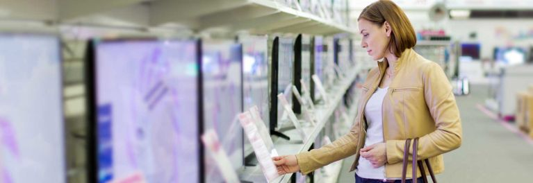 A photo of a woman looking over different brands of TVs while shopping at a store for the best TV