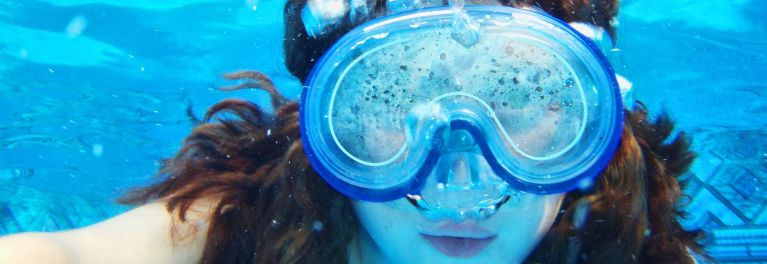 This is a photo of a girl wearing a mask underwater