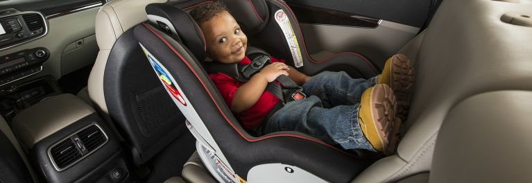Boy demonstrates best convertible car seats.