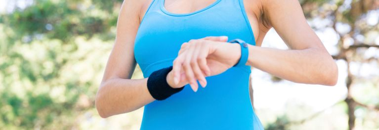 Woman in blue tank top checks blue fitness tracker.