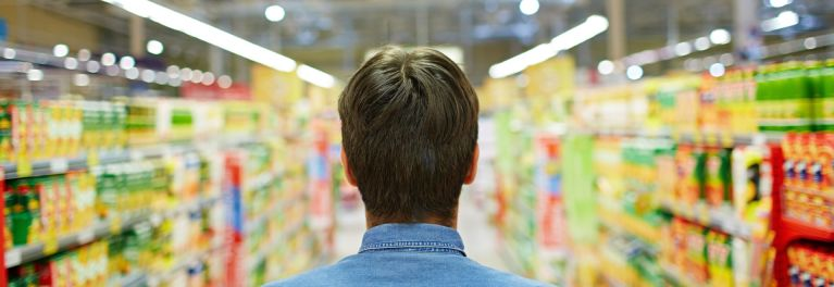 Man in supermarket grocery shopping. GMO labeling is a concern for many consumers.