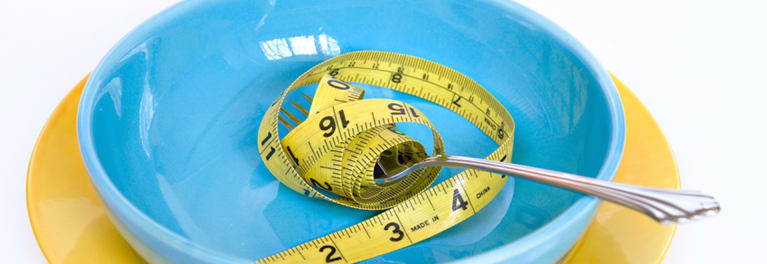 A blue bowl with a tape measure in it to illustrate the concept of portion sizes.