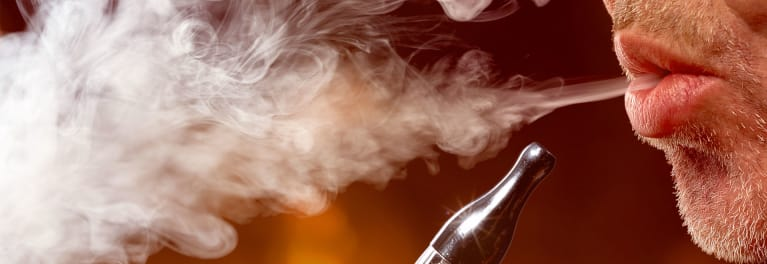 This is a photograph of a man exhaling e-cigarette vapor, or vaping, using an electronic nicotine delivery system (ENDS).