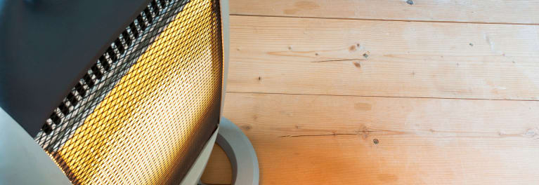 Space heater sitting on a wood floor.