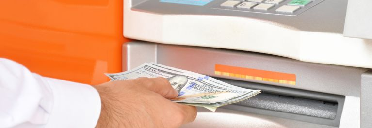 A customer receives cash from his banks automated teller machine to avoid ATM fees.