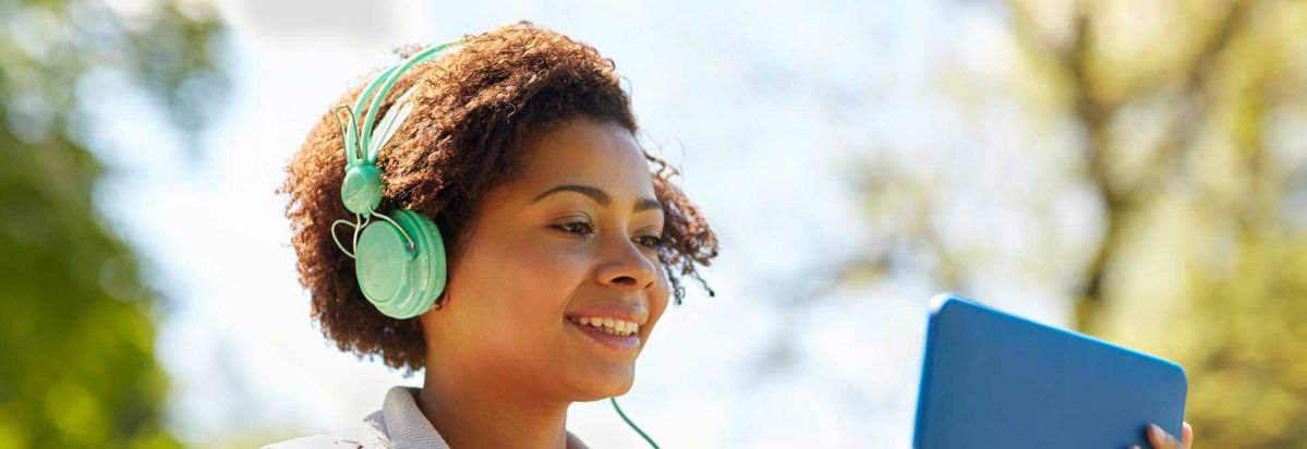 Photo of a woman wearing headphones watching her tablet  DirecTV Now is a streaming TV Consumer Reports