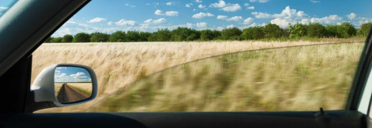 A view of a field through the passenger side window of a car.