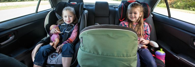 Three child car seats installed with children