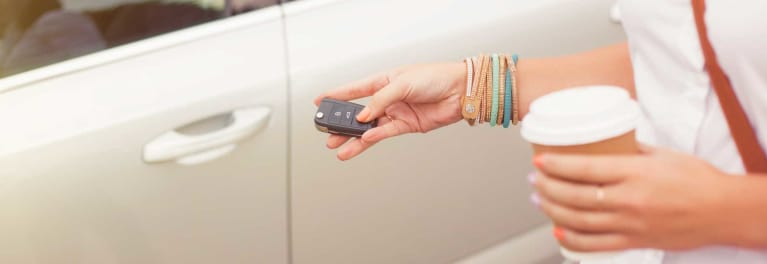 A teen using a key fob to open a car door.