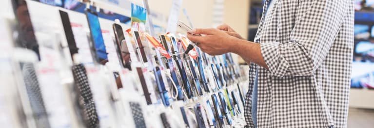 A man checking out cell phones in a store.