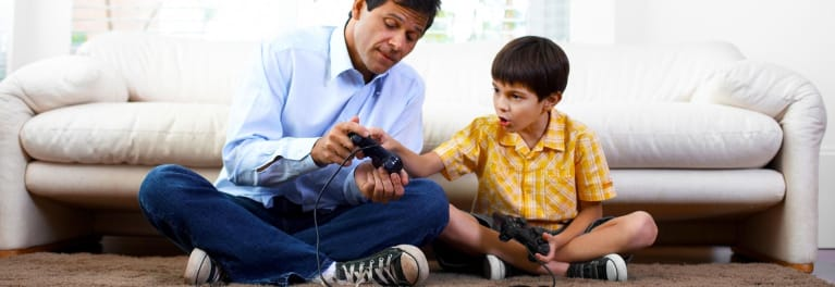 A parent and child play video games together.