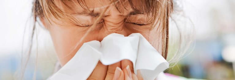 A woman blowing her nose. If you have an allergy to molds, a pile of fallen leaves may set of an allergic reaction.