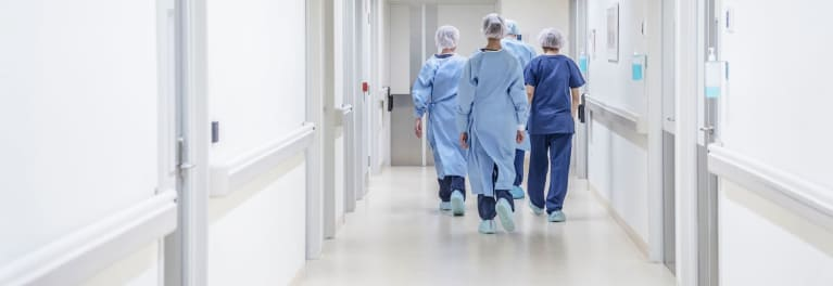 Medical staff walking down a hospital hallway.
