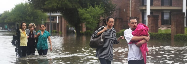 Flood victims wade through standing water.