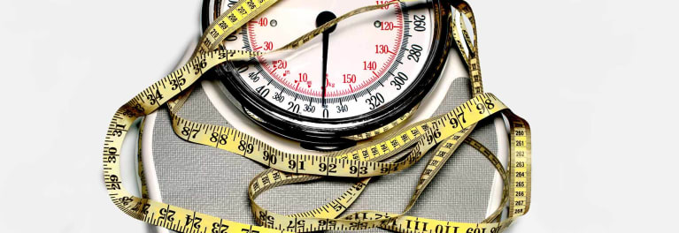 A scale and measuring tape to represent the health risks of being overweight.