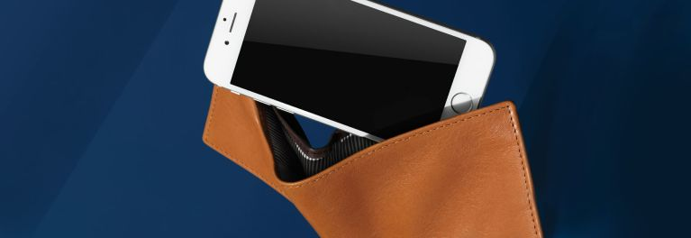 Cell phone coming out of brown wallet on a blue background