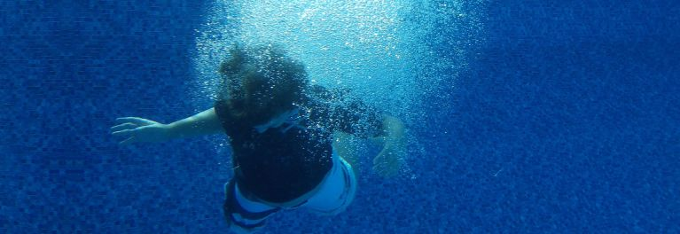 This is an underwater photo of a boy in a pool