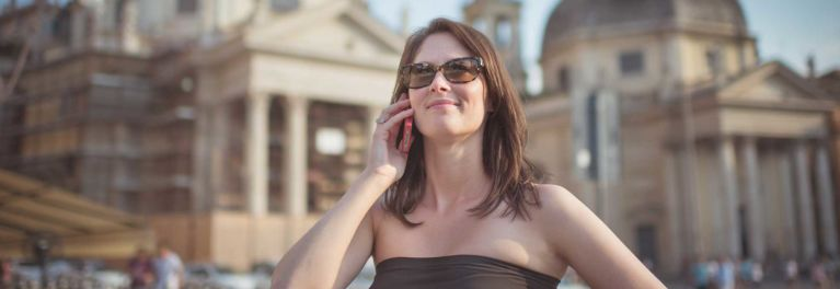A woman in a strapless dress using a smartphone abroad. She's happy because Consumer Reports showed her how to get cheap cell service when traveling outside the U.S.
