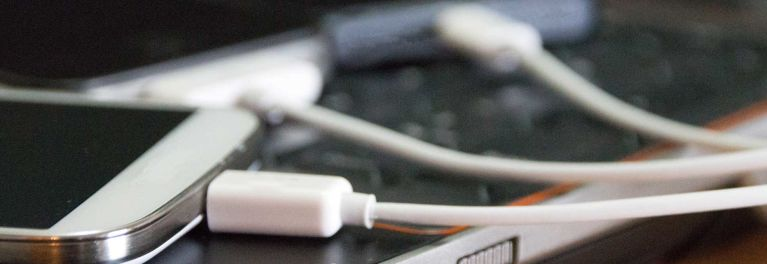 Phone chargers plugged into smartphones.