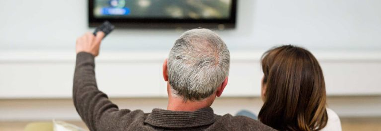 Photo of a couple watchin TV in a living-room setting. Many people struggle with poor Tv sound, and have difficulty hearing dialogue.