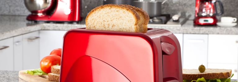 Shiny red small appliances on a kitchen countertop.