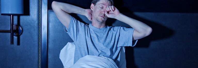 This is a photo of a sleepy man rubbing his eyes. Sleep disorders such as chronic insomnia and sleep apnea may go undiagnosed and untreated.