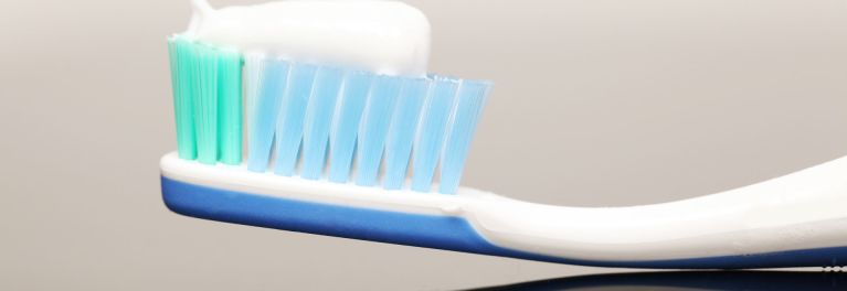 Hands squeezing toothpaste on a toothbrush.