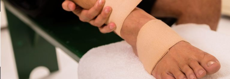 Wrapping a sprained ankle with elastic bandage.