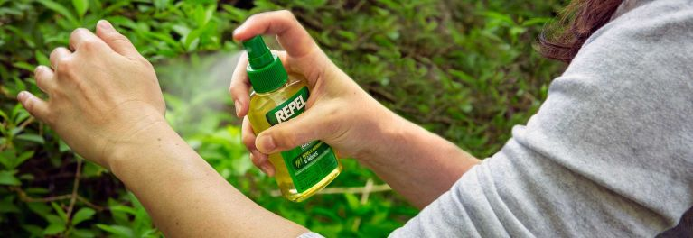 A person spraying on insect repellent.