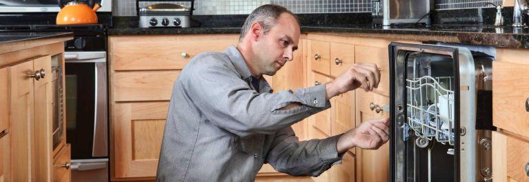 Appliance repair man fixing a dishwasher