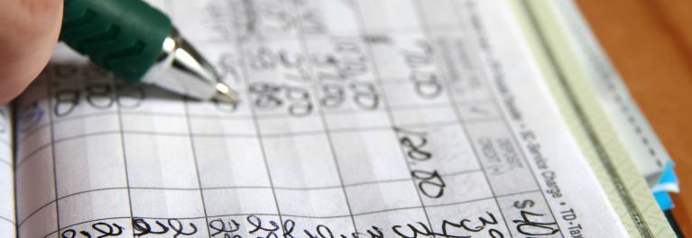 A consumer does the hard work of balancing her check register to avoid overdrafts.