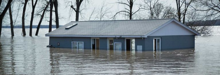 A one-story blue house halfway submerged in a flood