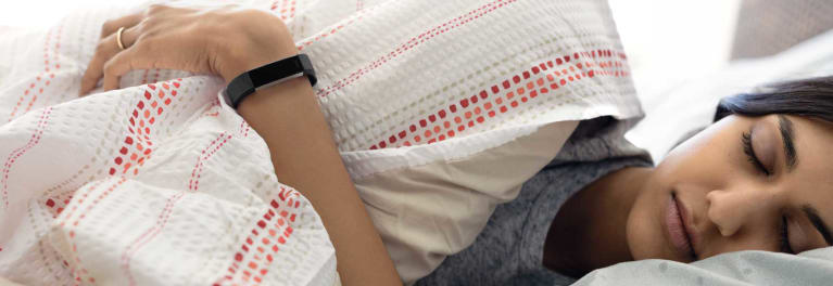 a woman asleep with Fitbit's Alta HR fitness tracker on her wrist
