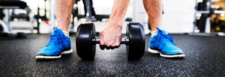 A man in blue sneakers about to lift a weight. Resistance training can be good for brain health.