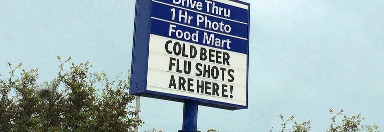 A photo of a drug store sign advertising that cold beer and flu shots are available at this store.