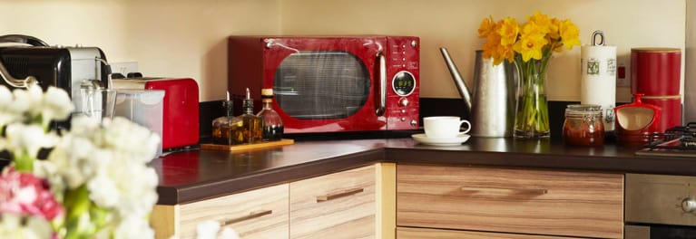 A red countertop microwave in a colorful kitchen.