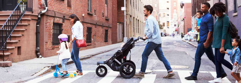 A man pushes one of the best strollers of 2018 in an urban area.