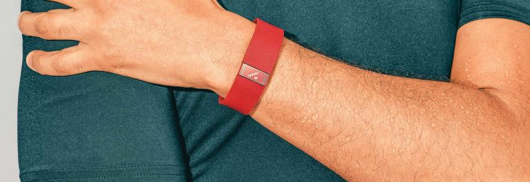 A photo of a red fitness tracker band on the wrist of a man.
